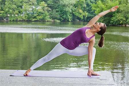 Mid adult woman performing yoga by river Stock Photo - Premium Royalty-Free, Code: 614-06002192