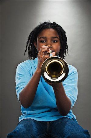 Portrait of black teenage boy playing trumpet, studio shot Stock Photo - Premium Royalty-Free, Code: 614-06002205