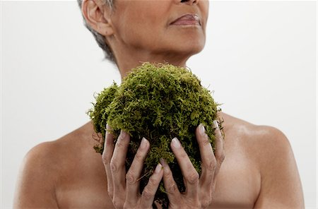 Senior woman holding plant, studio shot Stock Photo - Premium Royalty-Free, Code: 614-06002253