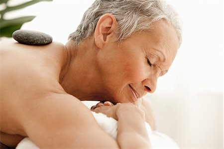 Senior woman receiving stone therapy Stock Photo - Premium Royalty-Free, Code: 614-06002277