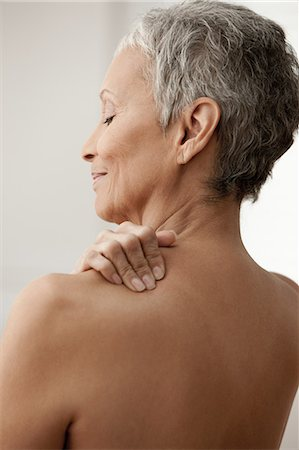 Senior woman massaging shoulder Stock Photo - Premium Royalty-Free, Code: 614-06002271