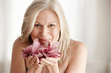 Mature woman holding flower, portrait Stock Photo - Premium Royalty-Free, Code: 614-06002281