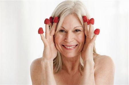 Mature woman wearing raspberries on fingers Stock Photo - Premium Royalty-Free, Code: 614-06002292