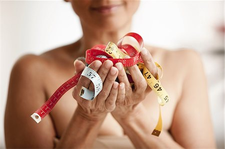 Senior woman holding measuring tapes in hands Stock Photo - Premium Royalty-Free, Code: 614-06002304