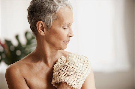 Senior woman exfoliating with mitt Stock Photo - Premium Royalty-Free, Code: 614-06002303