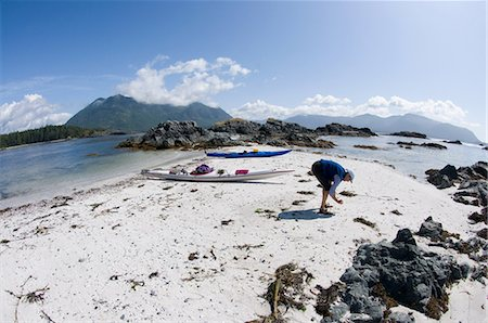 Woman looking for shells on beach, Esperanza Inlet, Vancouver Island, British Columbia, Canada Stock Photo - Premium Royalty-Free, Code: 614-06002332