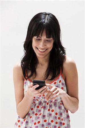 Smiling mature woman using cellphone, studio shot Stock Photo - Premium Royalty-Free, Code: 614-06002355