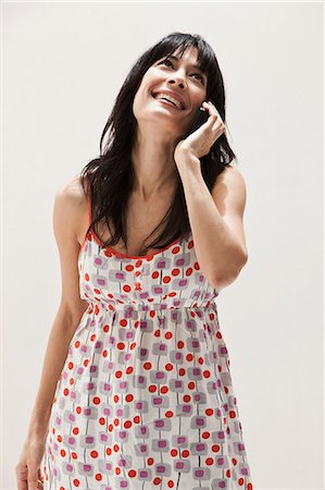 Smiling mature woman using cellphone, studio shot Stock Photo - Premium Royalty-Free, Code: 614-06002356