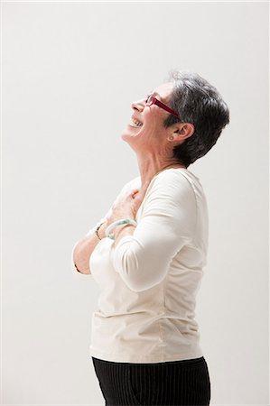 Side view of mature woman smiling, studio shot Stock Photo - Premium Royalty-Free, Code: 614-06002376