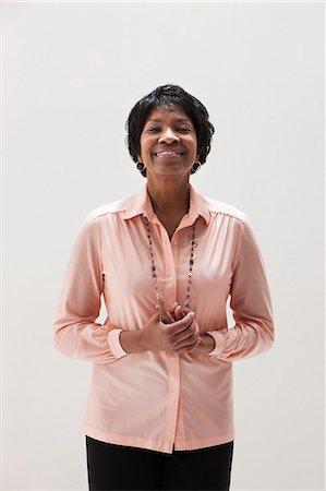 Portrait of smiling African American mature woman, studio shot Stock Photo - Premium Royalty-Free, Code: 614-06002380