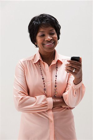 African American mature woman using cellphone, studio shot Stock Photo - Premium Royalty-Free, Code: 614-06002381