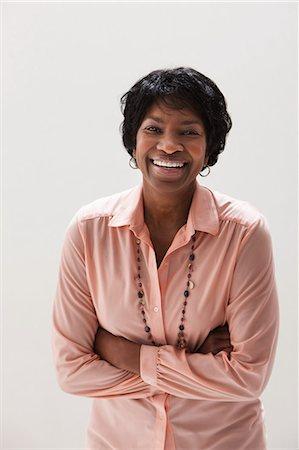 Portrait of smiling African American mature woman, studio shot Stock Photo - Premium Royalty-Free, Code: 614-06002383