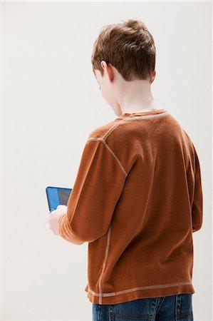 Boy in brown sweater playing hand held video game, studio shot Stock Photo - Premium Royalty-Free, Code: 614-06002396