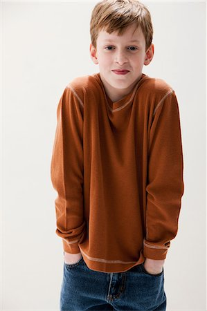 Boy in brown sweater with hands in pockets, studio shot Stock Photo - Premium Royalty-Free, Code: 614-06002392