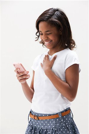 African American girl laughing and holding cellphone, studio shot Stock Photo - Premium Royalty-Free, Code: 614-06002408