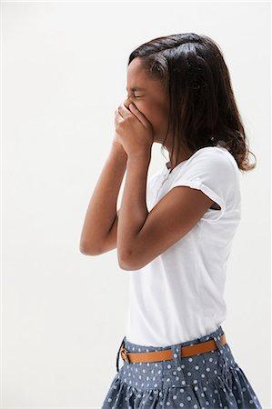 people coughing or sneezing - African American girl laughing, studio shot Stock Photo - Premium Royalty-Free, Code: 614-06002409
