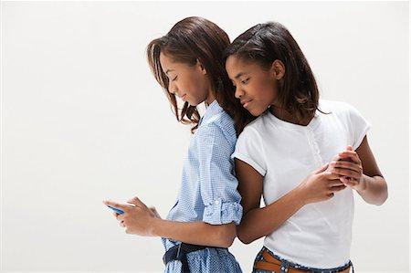 African American sisters using cellphones, studio shot Stock Photo - Premium Royalty-Free, Code: 614-06002420