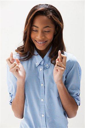 African American teenage girl with fingers crossed, studio shot Stock Photo - Premium Royalty-Free, Code: 614-06002423