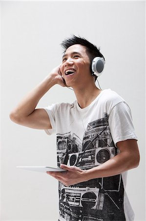 Young Asian man using digital tablet with headphones, studio shot Stock Photo - Premium Royalty-Free, Code: 614-06002447