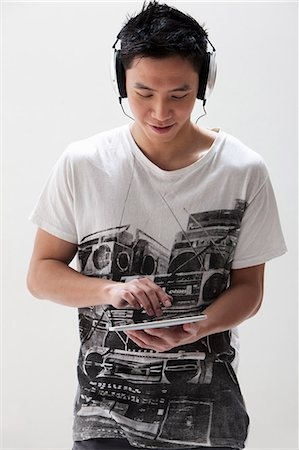 Young Asian man using digital tablet with headphones, studio shot Stock Photo - Premium Royalty-Free, Code: 614-06002448