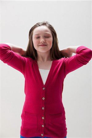 preteen girls stretching - Girl in red with hands behind head, studio shot Stock Photo - Premium Royalty-Free, Code: 614-06002449