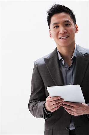 Young Asian businessman holding digital tablet, studio shot Stock Photo - Premium Royalty-Free, Code: 614-06002457