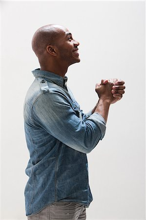 African American man with hands clasped, studio shot Stock Photo - Premium Royalty-Free, Code: 614-06002460