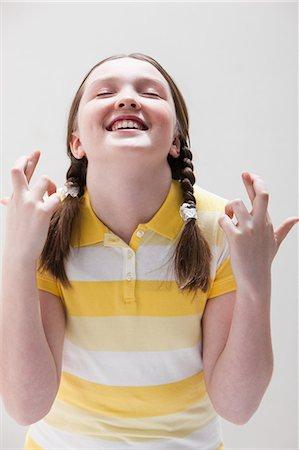 Girl with fingers crossed, studio shot Stock Photo - Premium Royalty-Free, Code: 614-06002461