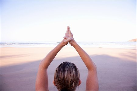 Close up of hands of woman in tree yoga pose on beach Stock Photo - Premium Royalty-Free, Code: 614-06002473