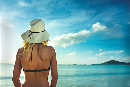 Rear view of woman in sunhat looking out to sea Stock Photo - Premium Royalty-Free, Code: 614-06002605