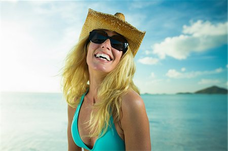 Happy woman in sunglasses and cowboy hat by the ocean Stock Photo - Premium Royalty-Free, Code: 614-06002608