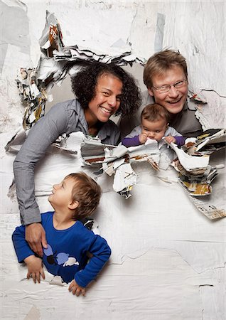 Happy family busting through a wall Stock Photo - Premium Royalty-Free, Code: 614-06002609