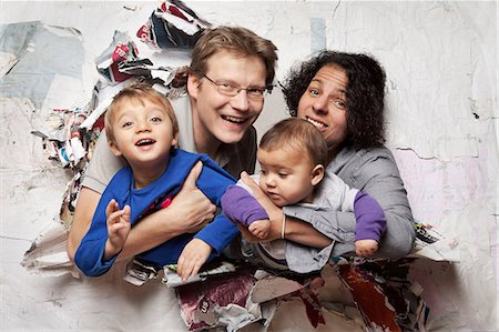 Happy family busting through a wall Stock Photo - Premium Royalty-Free, Code: 614-06002610