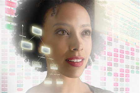 Woman surrounded by with holographic information Stock Photo - Premium Royalty-Free, Code: 614-06044014