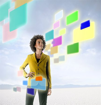 futuristic - Businesswoman looking at holographic screens in desert Stock Photo - Premium Royalty-Free, Code: 614-06044033