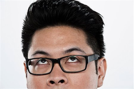 filipino - Young man looking up against white background, close up Stock Photo - Premium Royalty-Free, Code: 614-06044095