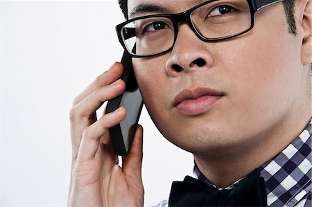 filipino (male) - Young man using cellphone against white background Stock Photo - Premium Royalty-Free, Code: 614-06044093