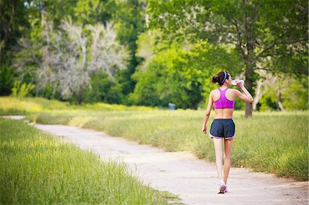 Young woman walking on path drinking mineral water Stock Photo - Premium Royalty-Free, Code: 614-06044168