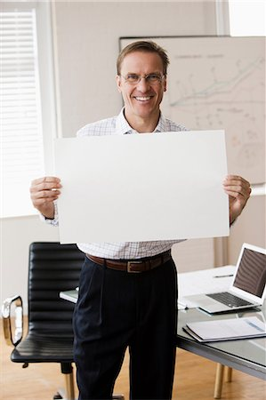 person holding sign - Mature businessman holding blank page in office Stock Photo - Premium Royalty-Free, Code: 614-06044350
