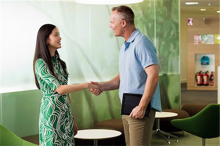 Mature man shaking hands with young woman in meeting Stock Photo - Premium Royalty-Free, Code: 614-06044588