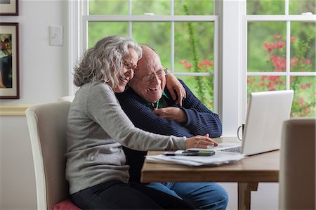 Senior couple using laptop at home, laughing Stock Photo - Premium Royalty-Free, Code: 614-06044610