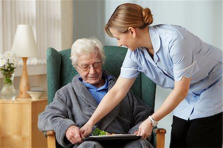 Carer bringing meal to senior man Stock Photo - Premium Royalty-Free, Code: 614-06043870