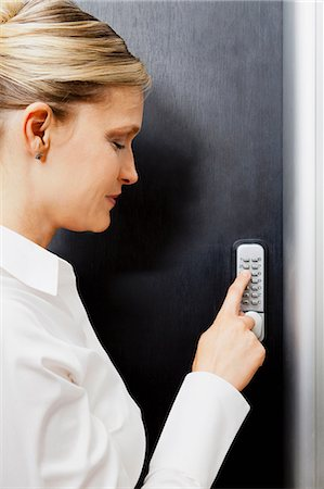 Woman pressing door keypad Stock Photo - Premium Royalty-Free, Code: 614-06043932