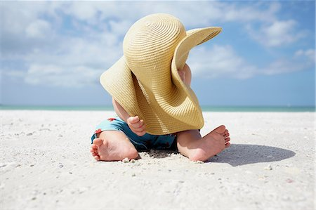 Baby boy playing with mother's sun hat on the beach Stock Photo - Premium Royalty-Free, Code: 614-06043987
