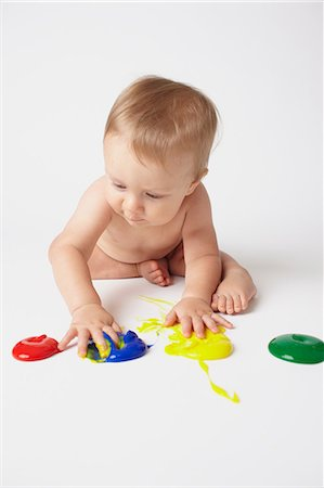 Baby putting hands in finger paints Stock Photo - Premium Royalty-Free, Code: 614-06043994