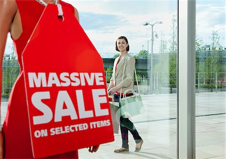 Woman looking at sale sign in shop window Stock Photo - Premium Royalty-Free, Code: 614-06116036