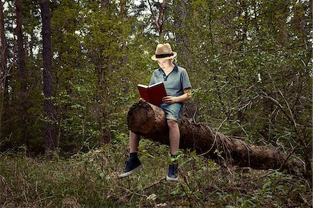 Boy sitting on tree trunk reading book Stock Photo - Premium Royalty-Free, Code: 614-06116043