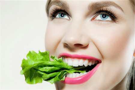 Young woman biting lettuce Stock Photo - Premium Royalty-Free, Code: 614-06116191