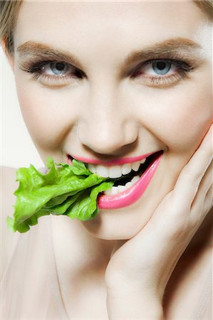 Young woman biting lettuce Stock Photo - Premium Royalty-Free, Code: 614-06116224