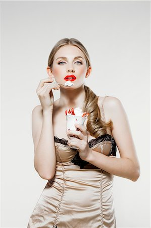 Young woman eating strawberries and cream Stock Photo - Premium Royalty-Free, Code: 614-06116220